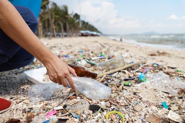 Vrijwilliger toeristische hand opruimen vuilnis en plastic puin op vuile strand in grote blauwe zak