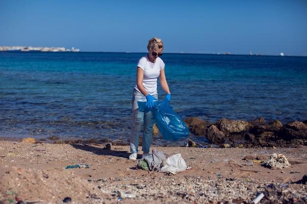 Vrijwilliger van de vrouw met grote blauwe zak die vuilnis op strand verzamelt. milieuvervuiling concept