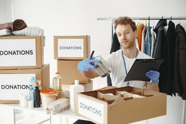 Vrijwilliger verzamelt dingen uit donaties. guy pakt dozen met dingen. de mens vergelijkt begiftiging.