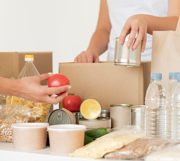 Vrijwilligers brengen ingeblikt voedsel en water voor donatie in een zak