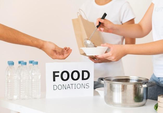 Vrijwilligers die donatievoedsel in kom overhandigen