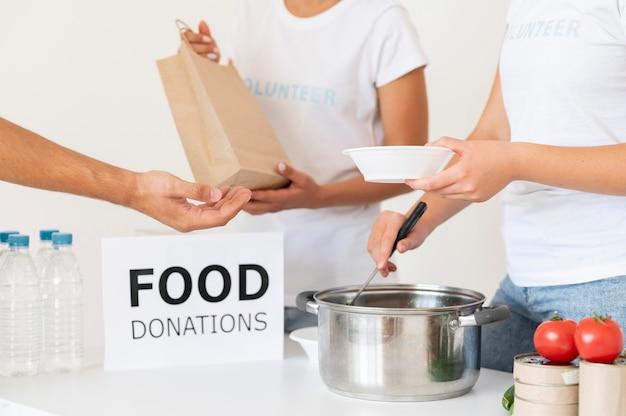 Vrijwilligers die donatievoedsel overhandigen