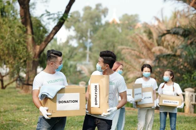 Vrijwilligers die dozen met kleding dragen die door mensen zijn geschonken tijdens een evenement in het plaatselijke park