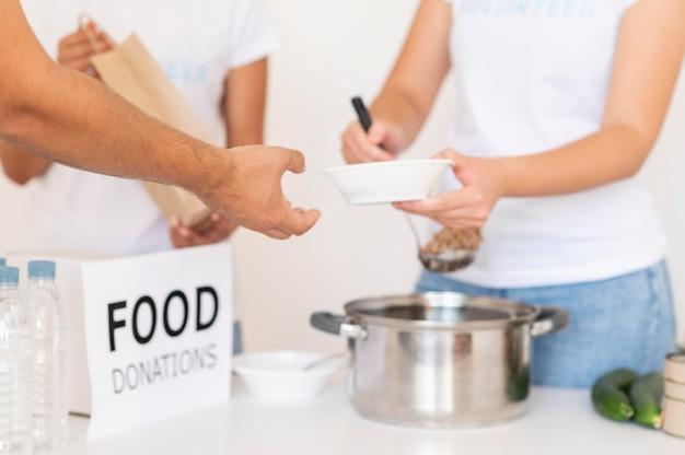Vrijwilligers die kom met voedsel overhandigen