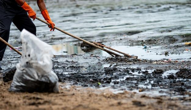 Vrijwilligers gebruiken de rake om het afval uit de zee te vegen. strandreiniger die afval verzamelt