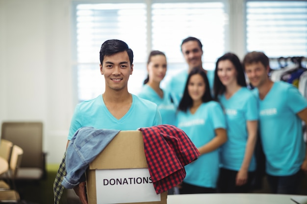 Vrijwilligers houden kleren in donatie doos