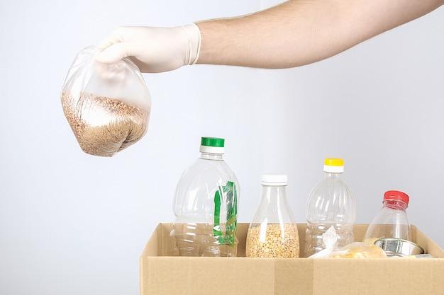 Vrijwilligers in handschoenen en masker met donatiebox met levensmiddelen op grijze achtergrond.