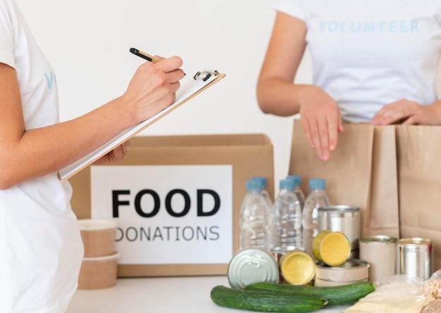 Vrijwilligers met blocnote die voedsel controleren op donatie