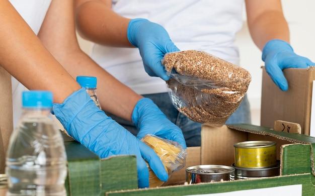 Vrijwilligers met handschoenen bereiden kratten met voedseldonaties voor