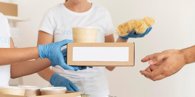 Vrijwilligers met handschoenen deelden dozen met voedsel uit om te doneren