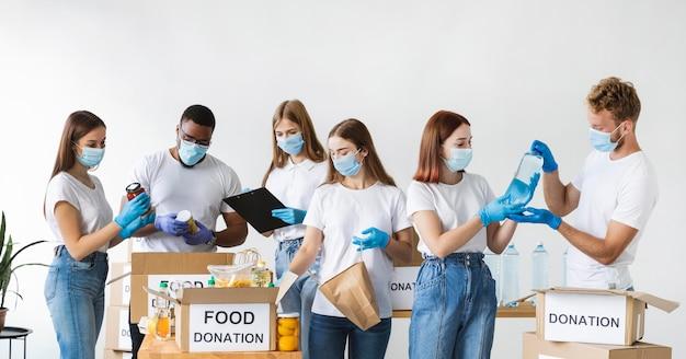 Vrijwilligers met handschoenen en medische maskers doos voorbereiden op donatie