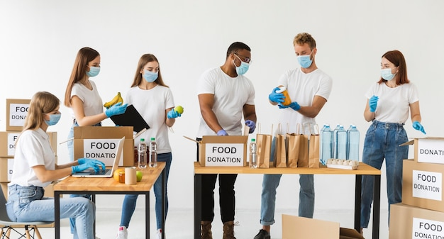 Vrijwilligers met medische maskers en handschoenen die dozen met voedsel voorbereiden voor donatie