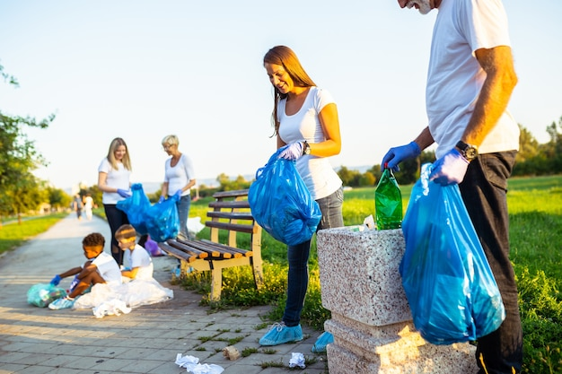 Vrijwilligers met vuilniszakken die vuilnis buitenshuis opruimen - ecologieconcept
