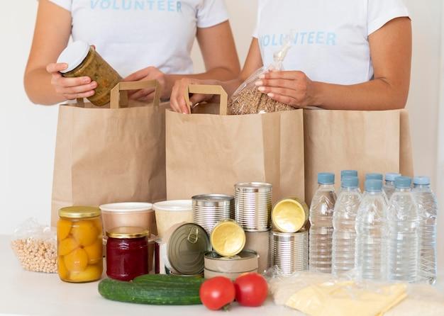 Vrijwilligers met zakken met voedsel en water voor donatie