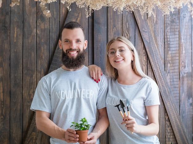 Vrijwilligers planten. glimlachend paar kamerplant en fundamentele tuingereedschap tonen.