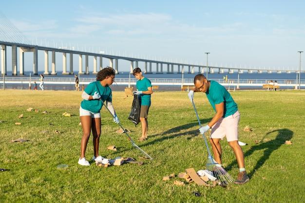 Vrijwilligers team die stadsgras schoonmaken van afval
