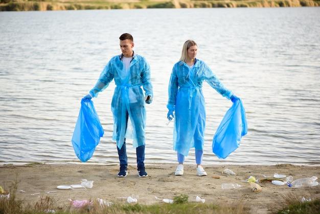 Vrijwilligers verzamelen plastic flessen in vuilniszak, ecologie, natuur, vervuiling, afval, zorg, vrijwilligerswerk voor liefdadigheid, gemeenschapsomgeving.