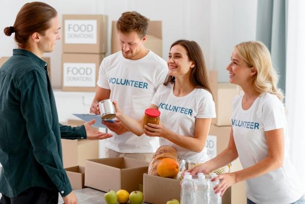 Vrijwilligers voor voedseldag die donaties uitdelen