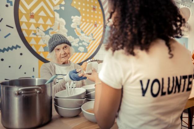 Vrijwilligerscentrum. ongelukkige arme vrouw die naar de aardige jonge vrouw kijkt terwijl ze wat te eten krijgt