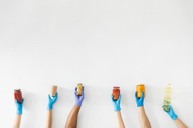 Vrijwilligershanden met handschoenen met proviand voor donatie