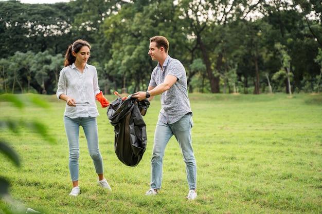 Vrijwilligersliefhebbers koppelen handschoenen aan om afval op te halen in het park om het milieu schoon te houden