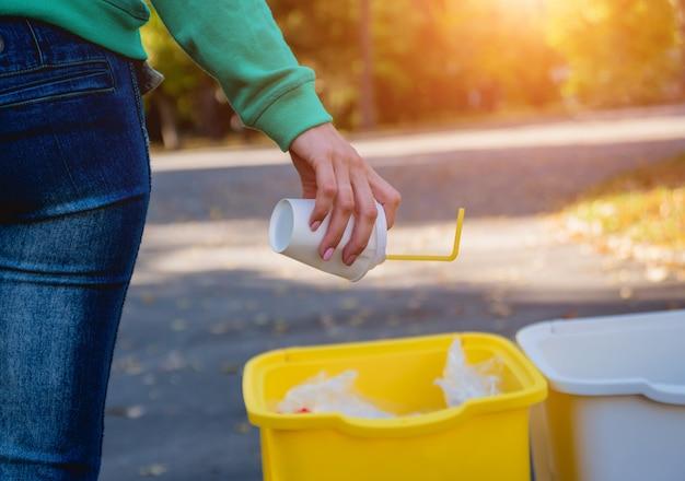 Vrijwilligersmeisje sorteert afval in de straat van het park. concept van recycling.