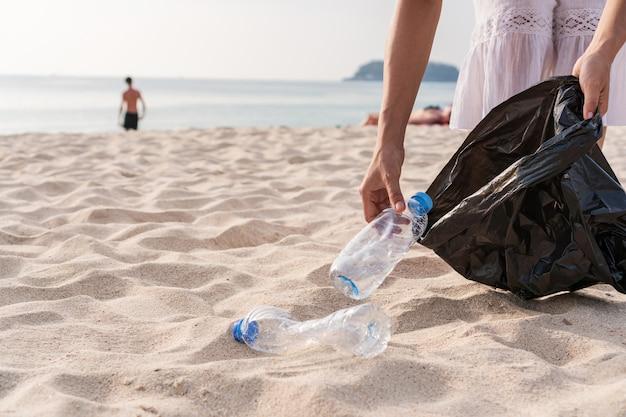 Vrijwilligersvrouw die huisvuil op het strand verzamelt. ecologie concept