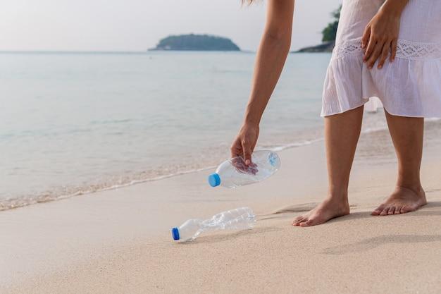 Vrijwilligersvrouw die huisvuil op het strand verzamelt
