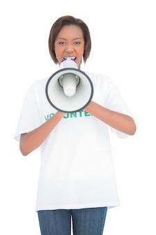 Vrijwilligersvrouw die in megafoon schreeuwt