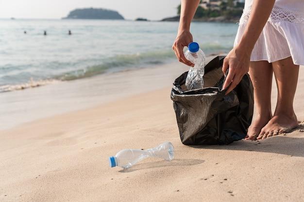 Vrijwilligersvrouw die vuilnis op het strand verzamelt. ecologie concept