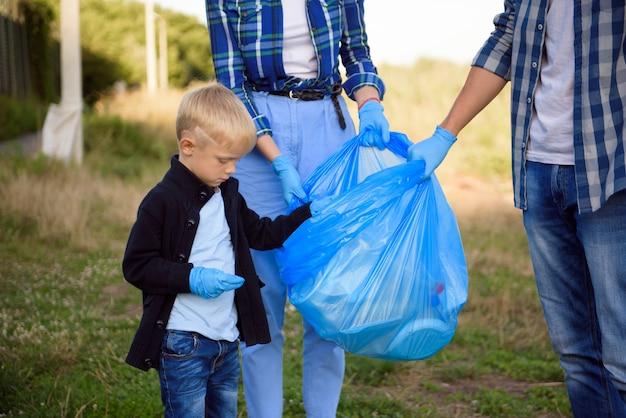 Vrijwilligerswerk, liefdadigheid, mensen en ecologieconcept, vrijwilligers die vuilniszak gebruiken bij het verzamelen van afval