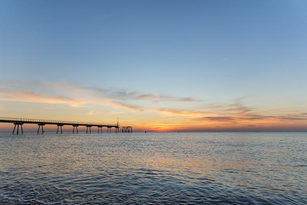 Vroeg in de ochtend een paar minuten voor zonsopgang zonsopgang op de zee met ponton blauwe lucht is geschilderd in oranje tinten
