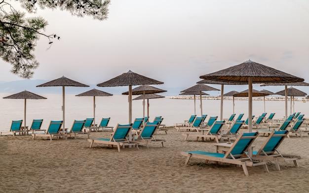 Vroeg in de ochtend ontspannende bankstoelen met parasols op zandstrand thasos-eiland griekenland