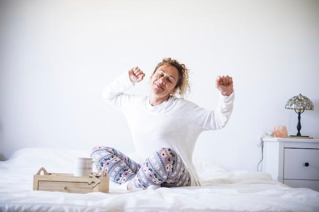 Vroeg in de ochtend wakker concept met gelukkige vrolijke blanke mooie volwassen vrouw die zich uitstrekt en glimlacht - witte kleuren en licht in de slaapkamer thuis of hotel - thuis blijven quarantaine