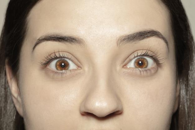 Vroeg me af. close-up van het gezicht van een mooie blanke jonge vrouw, focus op de ogen. menselijke emoties, gezichtsuitdrukking, cosmetologie, lichaams- en huidverzorgingsconcept.