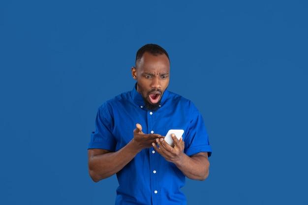 Vroeg me af met behulp van de telefoon. zwart-wit portret van jonge afro-amerikaanse man geïsoleerd op blauwe studio muur.