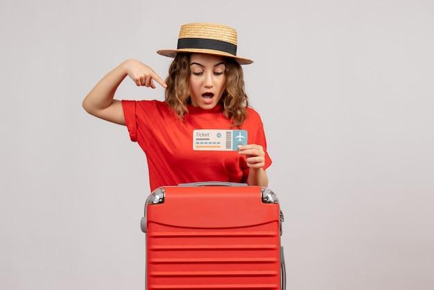 Vroeg vakantiemeisje zich af met haar koffertje wijzend op ticket