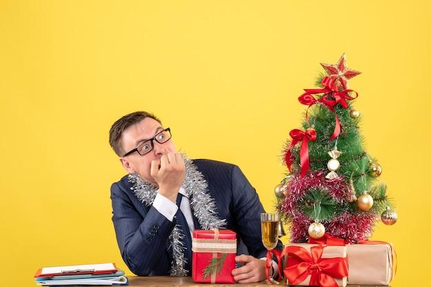 Vroeg zich af man met bril zittend aan de tafel in de buurt van kerstboom en cadeautjes op geel