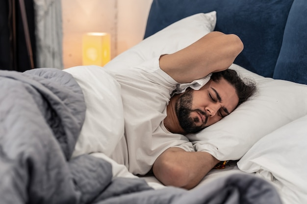 Vroege morgen. aardige knappe man die kussens vasthoudt terwijl hij 's ochtends slaapt