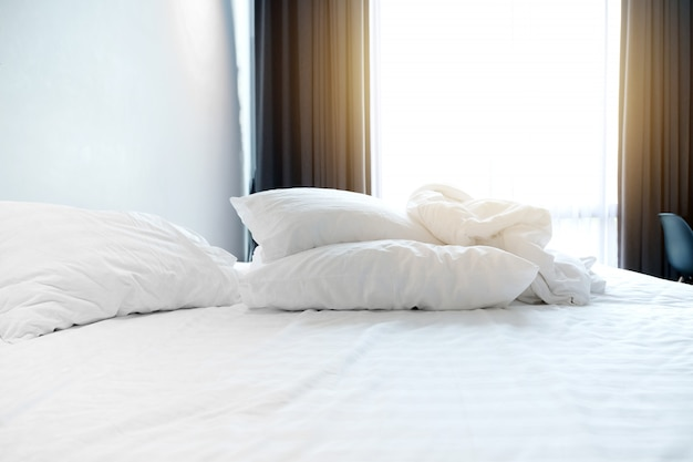 Vroege ochtend in witte bedruimte met verfrommeld dekbed en hoofdkussen op bed.