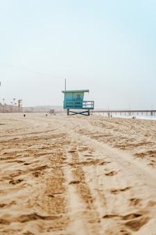 Vroege ochtendzonsopgang en zachte waas op de golven van manhattan beach en reddingstorens in los angeles