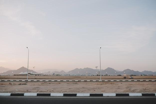 Vroege ochtendzonsopgang, landschap met bergen op weg van tropisch land. blauwe lucht, zomer, natuur, ver reizen.