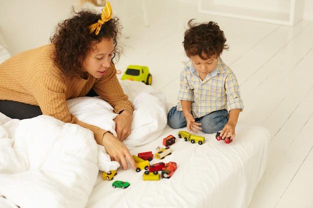 Vroege ontwikkeling, kinderjaren en moederschap. binnen schot van nieuwsgierig schattig baby kind zittend op de vloer spelen met veel kleurrijke speelgoedauto's op wit laken, moeder naast hem, kijken naar hem spelen