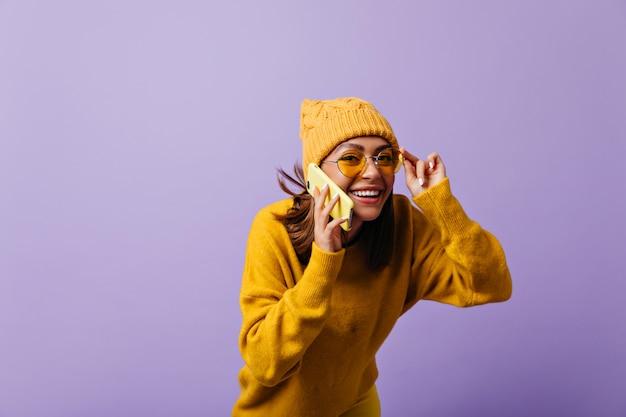 Vrolijk 21-jarig meisje met kastanjebruin haar heeft een grappig, interessant telefoongesprek. lachende vrouw kijkt door gele zonnebril met interesse poseren voor portret