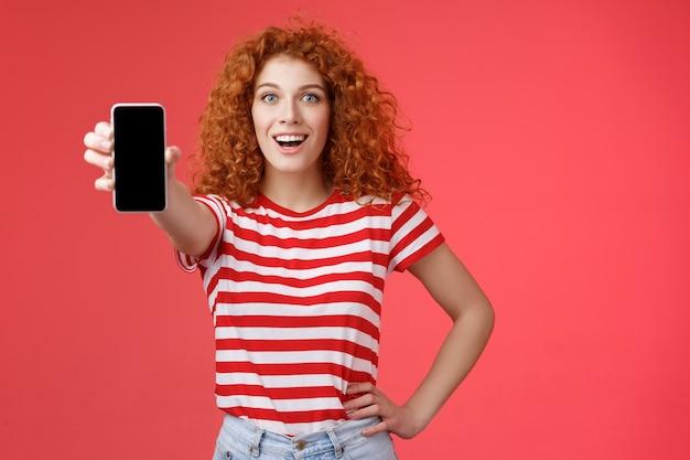 Vrolijk aantrekkelijk charismatisch europees roodharig meisje met krullend kapsel toont smartphonescherm glimlachend promoot app-advies goede toepassing sociale media pagina rode achtergrond.