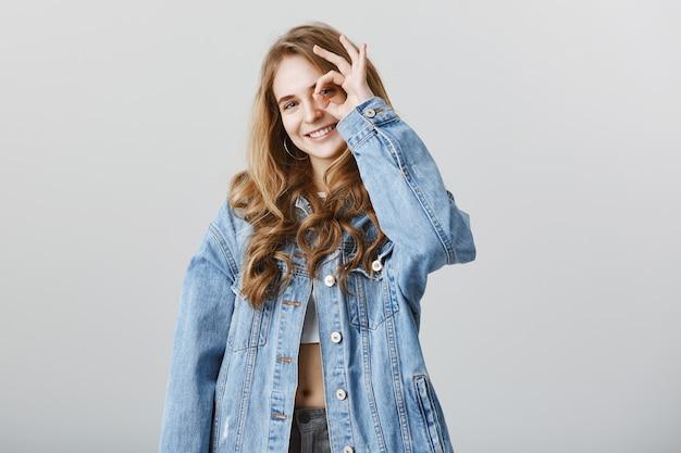 Vrolijk aantrekkelijk meisje dat ok gebaar toont, geen probleem, goed gedaan, uitstekend