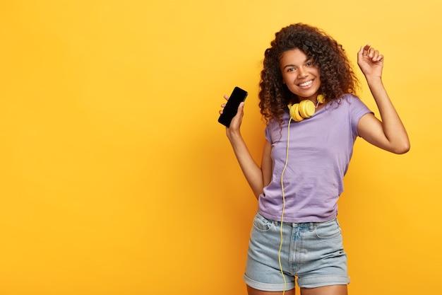 Vrolijk aantrekkelijk meisje met krullend haar, donkere huid, geniet van coole liedjes gedownload van online website, draagt een koptelefoon