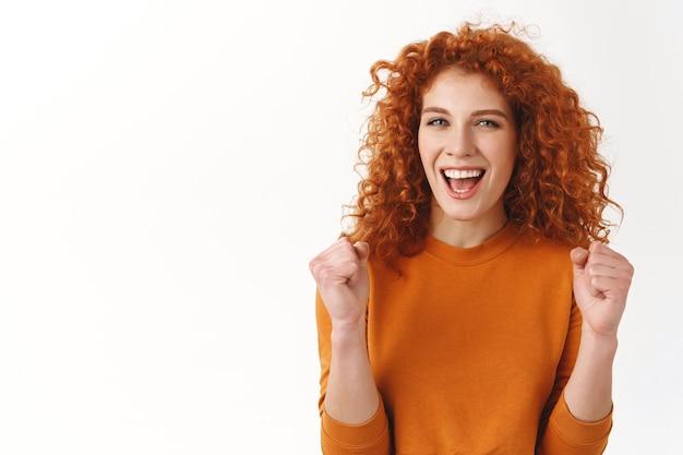 Vrolijk aantrekkelijk stijlvol kaukasisch roodharig meisje dat voor je wroet, triomfeert en zich verheugt over winnen, doel bereikend vrolijk lachend, vuistpomp van succes en geluk