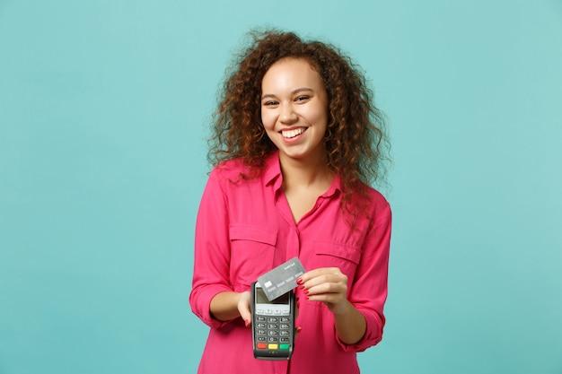 Vrolijk afrikaans meisje houdt draadloze moderne bankbetaalterminal vast om creditcardbetalingen te verwerken, geïsoleerd op blauwe turkooizen achtergrond. mensen emoties, lifestyle concept. bespotten kopie ruimte.