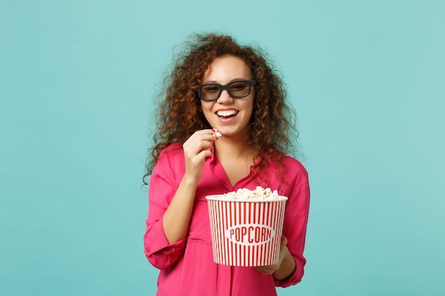 Vrolijk afrikaans meisje in 3d imax bril kijken naar film film en houden popcorn geïsoleerd op blauwe turquoise muur achtergrond in studio. mensen emoties in de bioscoop, lifestyle concept. bespotten kopie ruimte.